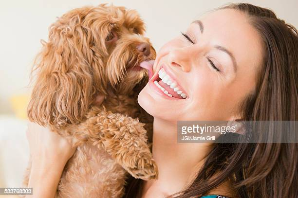 Caucasian woman playing with pet dog