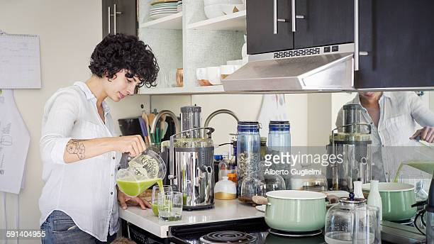 Caucasian woman pouring juice in kitchen