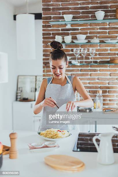 Caucasian woman pouring sauce on pasta in kitchen