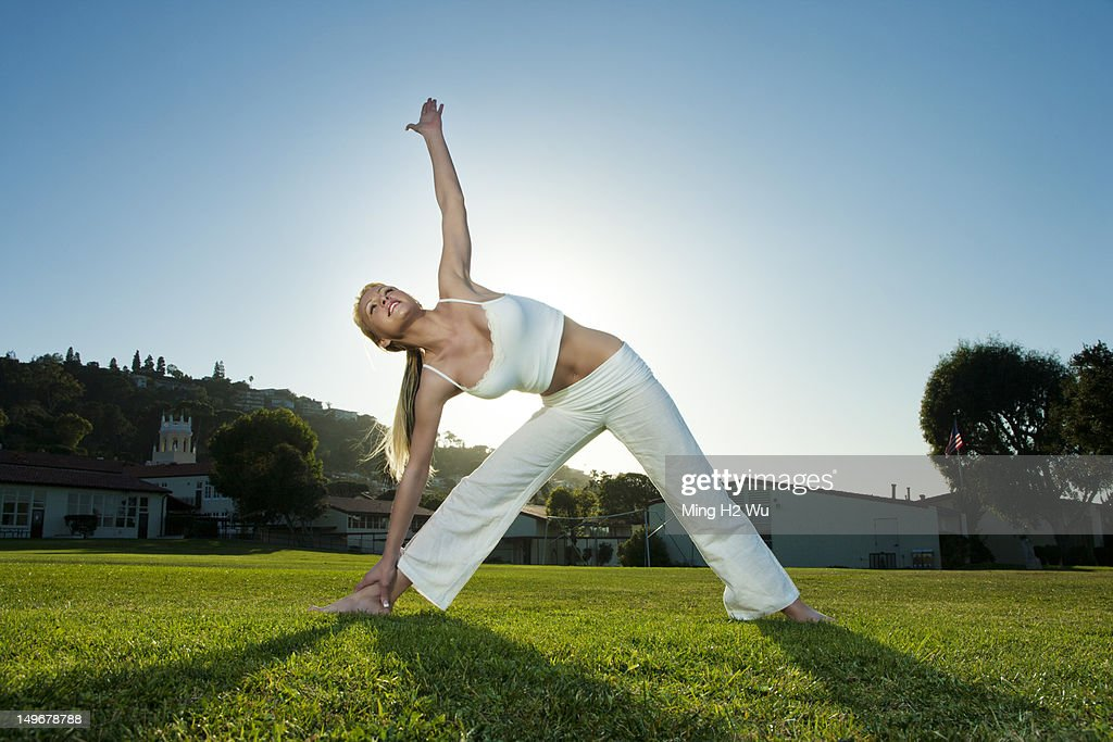 Caucasian woman practicing yoga in field : Stock Photo