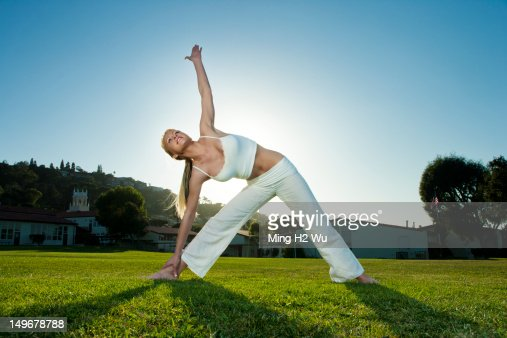 Caucasian woman practicing yoga in field : Foto de stock