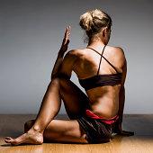 Caucasian woman practicing yoga in studio