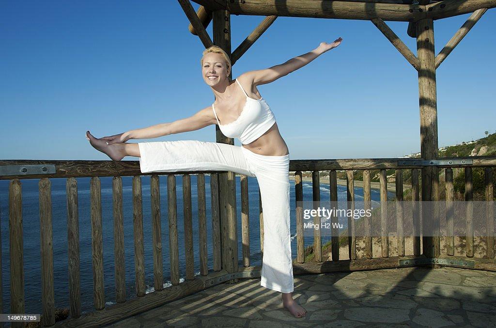 Caucasian woman practicing yoga near ocean : Stock Photo