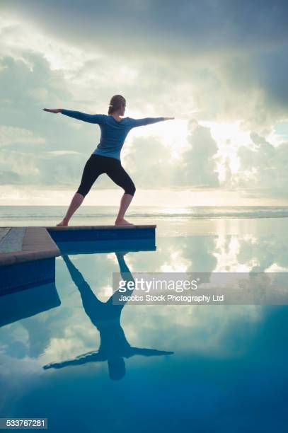 Caucasian woman practicing yoga near swimming pool