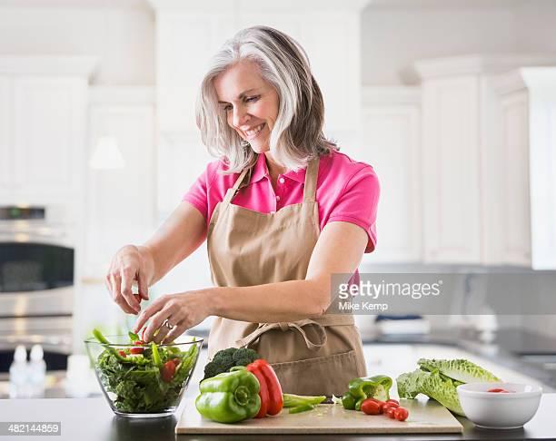 Caucasian woman preparing salad in kitchen