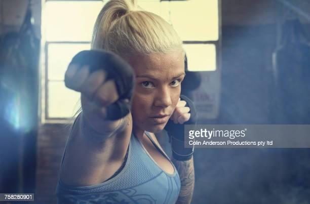 Caucasian woman punching in gymnasium