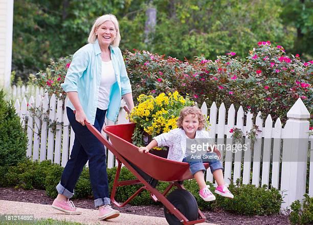 Caucasian woman pushing granddaughter in wheelbarrow