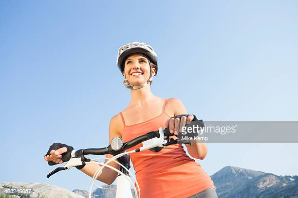 Caucasian woman pushing mountain bike