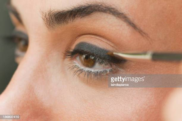 Caucasian woman putting on eyeliner