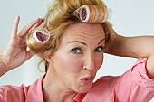 Caucasian woman putting rollers in her hair