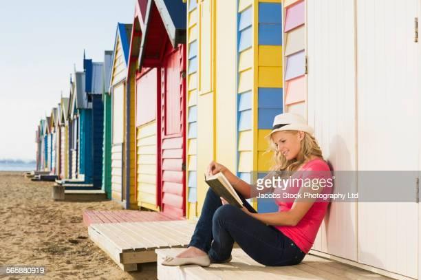 Caucasian woman reading book near colorful beach hut