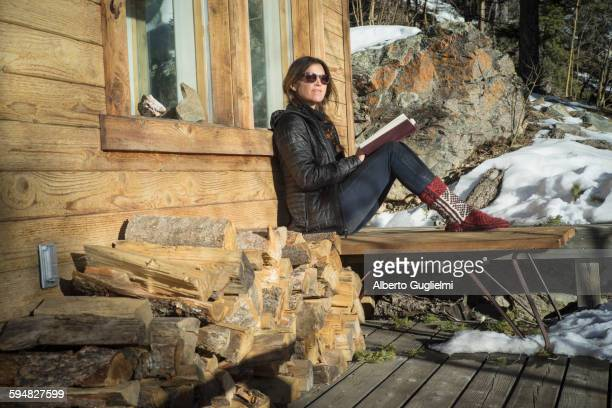 Caucasian woman reading book on cabin porch