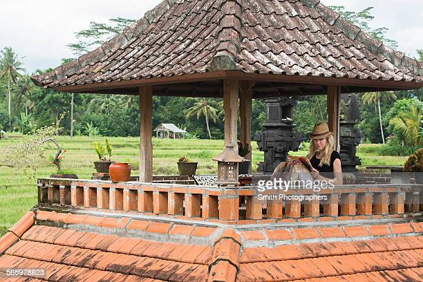 Caucasian woman reading book on rooftop balcony