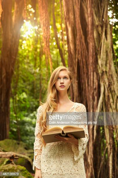 Caucasian woman reading book under banyan trees