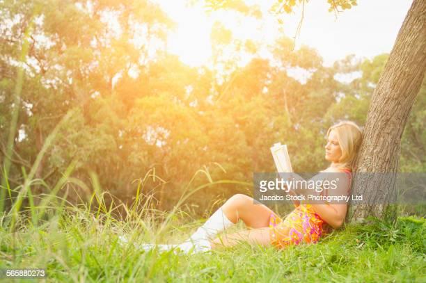 Caucasian woman reading book under tree in field