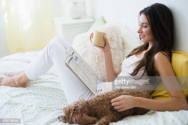 Caucasian woman reading magazine with pet dog in bed