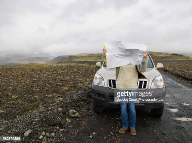 Caucasian woman reading map on remote road during road trip
