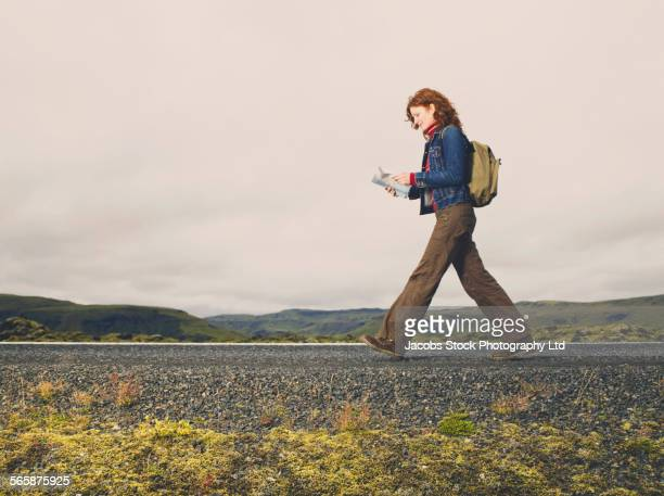 Caucasian woman reading map on remote road