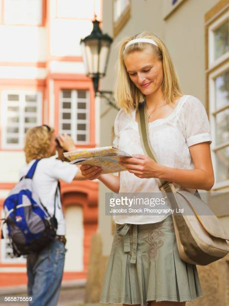 Caucasian woman reading map outdoors
