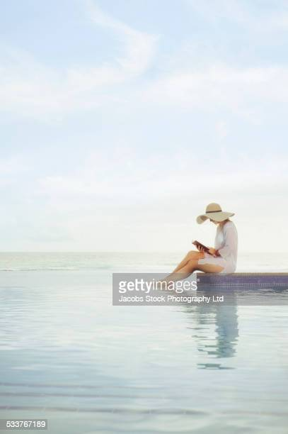 Caucasian woman relaxing at swimming pool