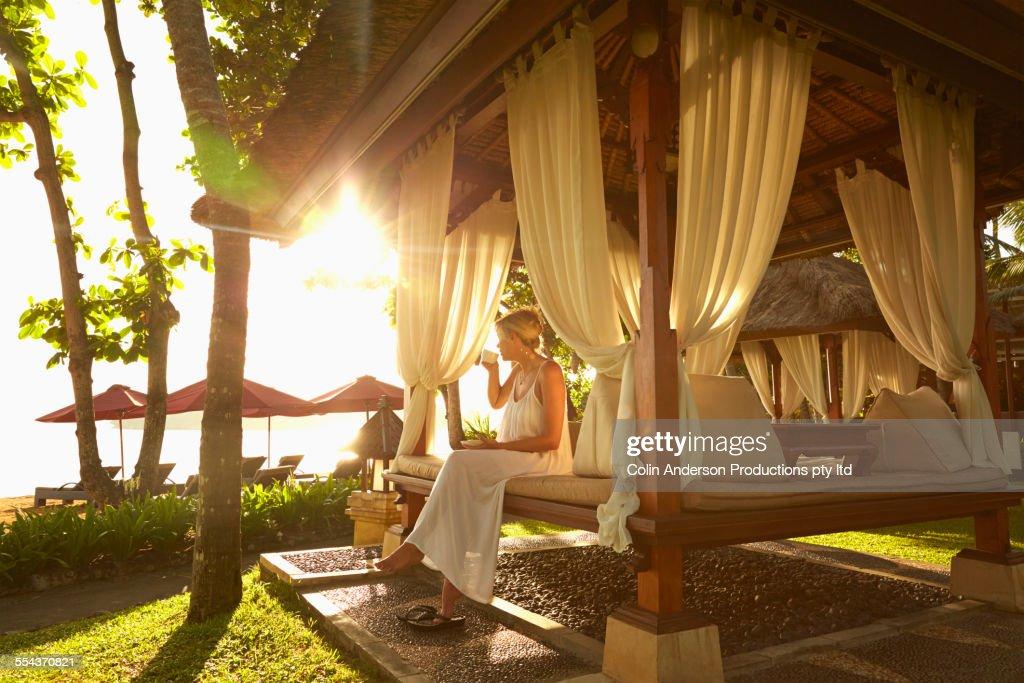 Caucasian woman relaxing in cabana on tropical beach