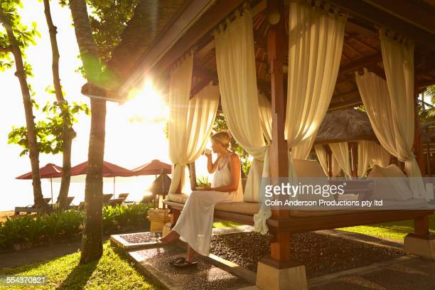 Caucasian woman relaxing in cabana on tropical beach