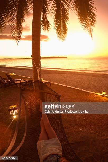 Caucasian woman relaxing in hammock under palm tree
