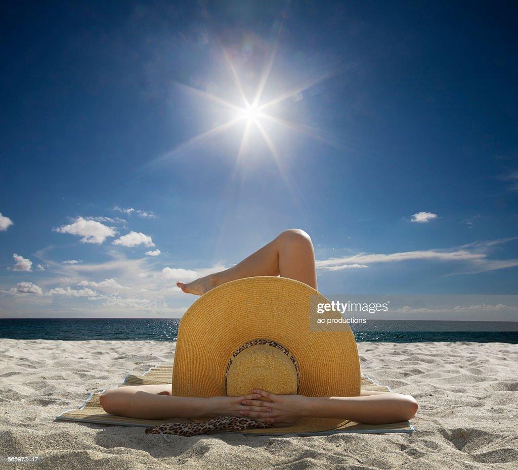 Caucasian woman relaxing on beach under blue sky