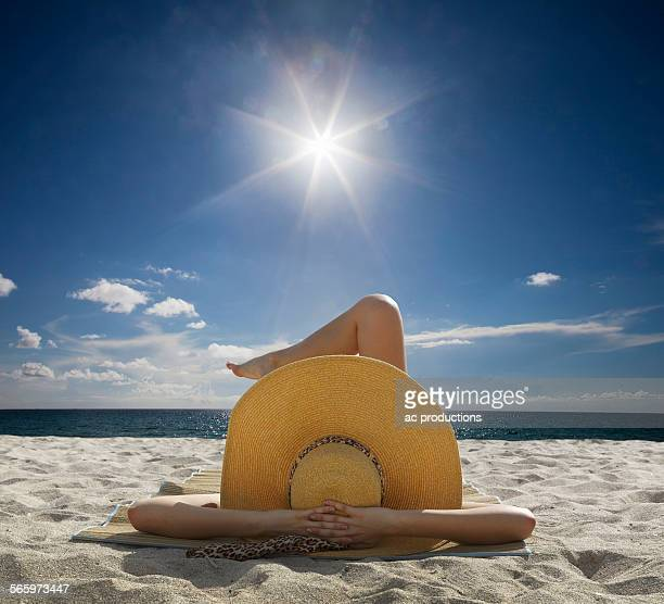 Caucasian woman relaxing on beach under blue sky