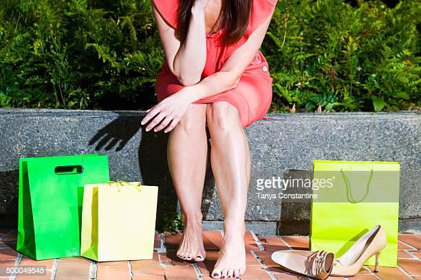 Caucasian woman resting feet after shopping