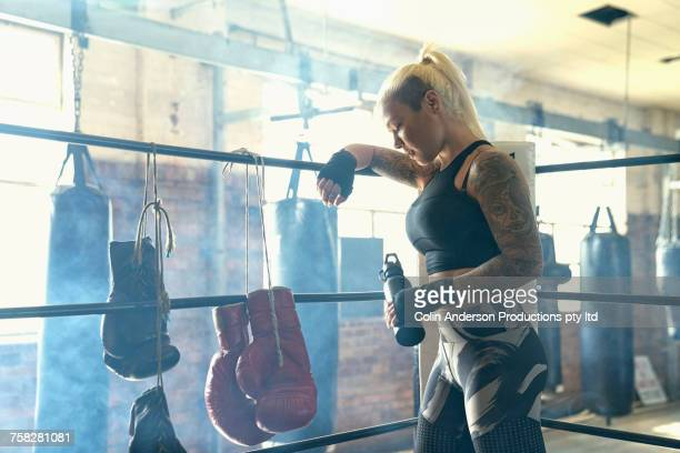 Caucasian woman resting in boxing ring