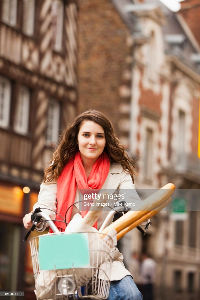 Caucasian woman riding bicycle with bread in basket