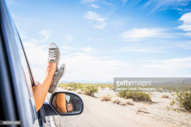 Caucasian woman riding in car with feet up on window