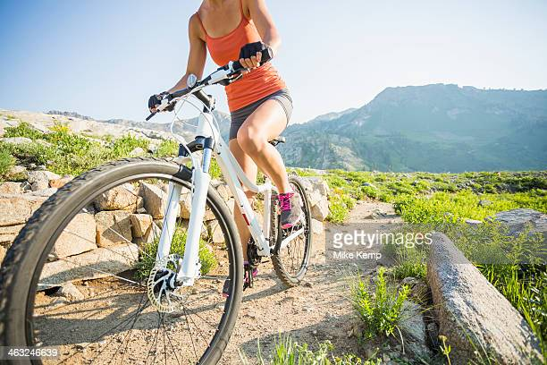 Caucasian woman riding mountain bike on rocky trail