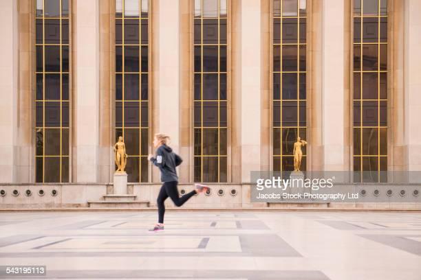 Caucasian woman running in courtyard