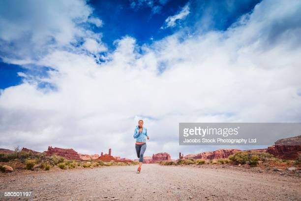 Caucasian woman running in desert landscape
