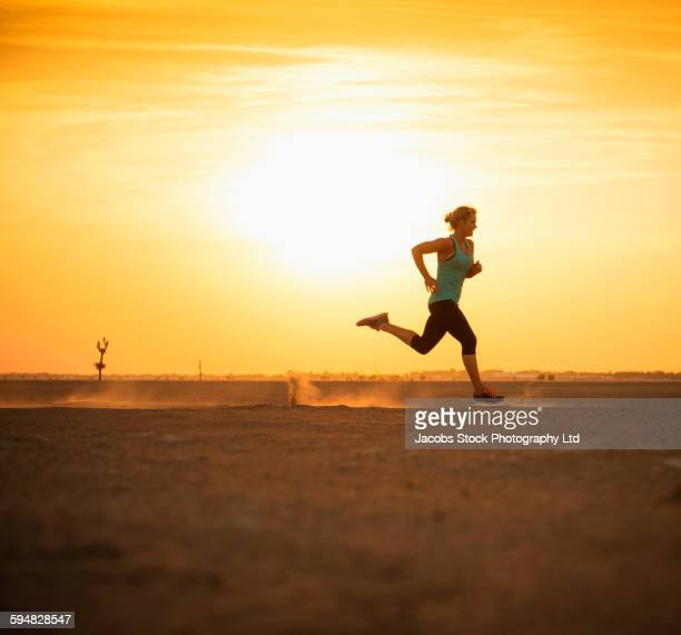 Caucasian woman running in desert