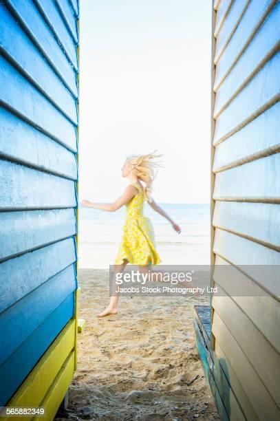 Caucasian woman running near colorful beach hut