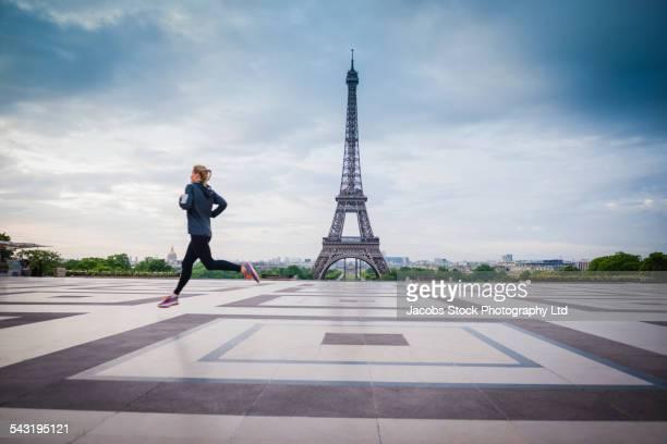 Caucasian woman running near Eiffel Tower, Paris, France