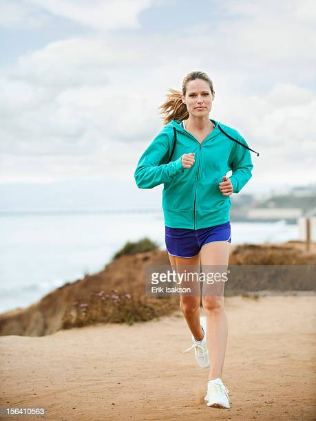 Caucasian woman running on beach