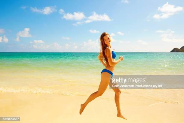 Caucasian woman running on beach