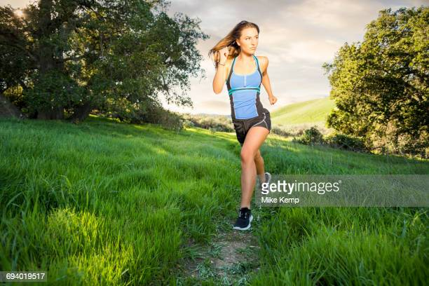 Caucasian woman running on hill