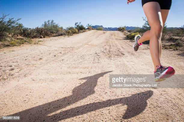 Caucasian woman running on remote dirt road