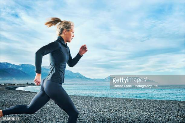 Caucasian woman running on rocky beach