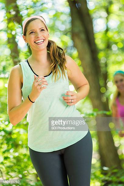 Caucasian woman running or exercising outdoors at park