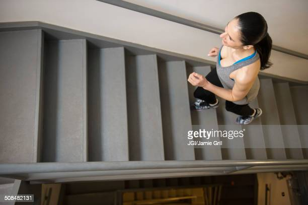 Caucasian woman running up stairs