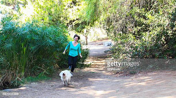 Caucasian woman running with dog on dirt path