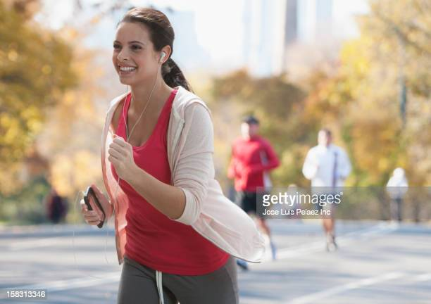 Caucasian woman running with mp3 player in park