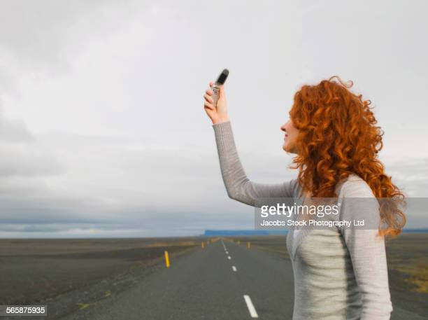 Caucasian woman searching for cell phone signal on remote road