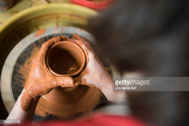 Caucasian woman shaping pottery clay on wheel